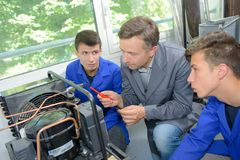 Apprentice electricians looking at electrical unit with instructor Stock Images