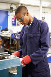 Apprentice Engineer Working On Factory Floor. By Himself stock photos