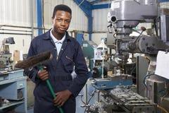 Apprentice In Engineering Factory Sweeping Floor Stock Photo