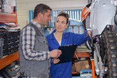 Apprentice female motorbike mechanic with mentor in garage. Apprentice female motorbike mechanic with her mentor in the garage Stock Photos