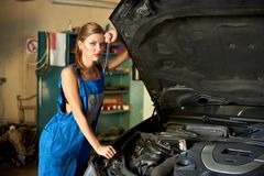 Apprentice female is next to car, holds spanner in hand royalty free stock image