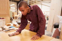 Apprentice Finishing Wood In Carpentry Workshop Stock Photo