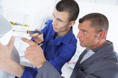 Apprentice fixing something with help teacher Stock Photography