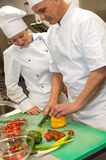 Apprentice learning cutting vegetables from chef Stock Image
