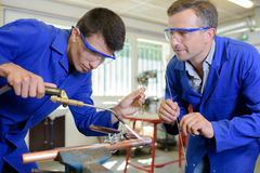 Apprentice learning to use blow torch Royalty Free Stock Image