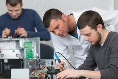 Apprentice male technician soldering lan switch router. Man Stock Photography