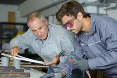 Apprentice and man soldering and repair. Apprentice and men soldering and repair men royalty free stock image
