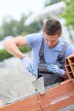 Apprentice of masonry laying bricks Royalty Free Stock Photography