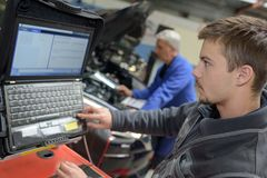 Apprentice mechanic diagnosing car problem with computer. Team Royalty Free Stock Images