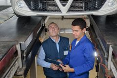 Apprentice mechanic repairing car monitored by mentor. Apprentice mechanic repairing a car monitored by mentor Stock Photos