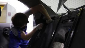 Apprentice Mechanic Working On Car removes the seat belt.