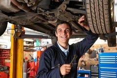 Apprentice Mechanic Working On Car stock photo