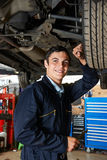 Apprentice Mechanic Working Under Car Stock Image