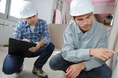 Apprentice and mentor working at construction site. Apprentice stock photos