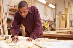 Apprentice Planing Wood In Carpentry Workshop Royalty Free Stock Image