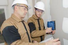 Apprentice plasterer sanding wall. Apprentice plasterer sanding the wall Stock Images