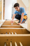 Apprentice Plumber Fitting Central Heating System In House. Apprentice Plumber Fits Central Heating System In House royalty free stock photography
