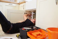 Apprentice plumber fixing the kitchen sink in a home Royalty Free Stock Image