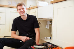 Apprentice plumber sitting in a kitchen, portrait Royalty Free Stock Image
