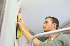 Apprentice Putting Wallpaper On The Wall Stock Image