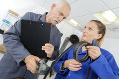 Apprentice showing length rubber to tutor. Apprentice showing length of rubber to tutor Royalty Free Stock Image