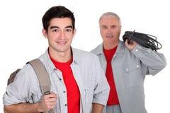 Apprentice standing near his boss. An apprentice standing near his boss stock image