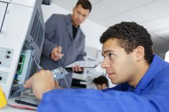 Apprentice technician repairing printer at business place at work Stock Photos