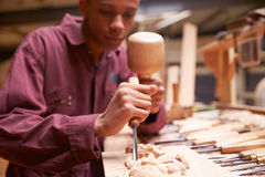 Apprentice Using Chisel To Carve Wood In Workshop Stock Image
