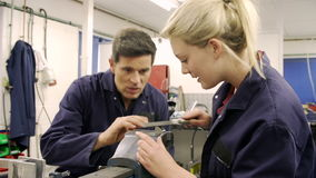 Apprentice Using Metal File On Factory Floor stock footage