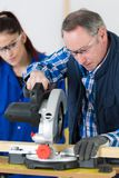 Apprentice watching how to use circular saw. Circular royalty free stock photo