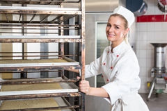 Apprentice or worker in bakery push Rack with dough Royalty Free Stock Photos