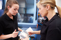 Apprentice Working With Female Engineer On CNC Machinery Royalty Free Stock Photo