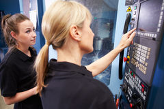 Apprentice Working With Female Engineer On CNC Machinery Royalty Free Stock Photography