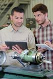 Apprentice working on milling machine stock photography