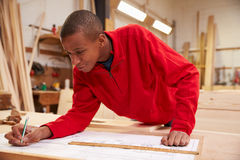 Apprentice Working With Plans In Carpentry Workshop Stock Photos