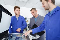 Apprentices around the printer Stock Image