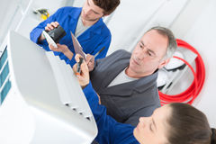 Apprentices fixe industrial compressor unit as supervisor watches Stock Photo