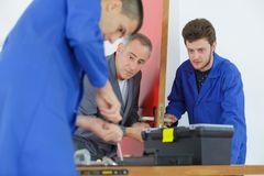Apprentices learning to fit door mechanism stock images