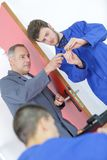 Apprentices learning to fix door with mentor. Apprentices learning to fix a door with mentor Stock Photo