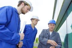 Apprentices and teacher near building. Apprentices stock photo