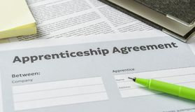 Apprenticeship agreement with a pen on a desk. An Apprenticeship agreement with a pen on a desk royalty free stock images