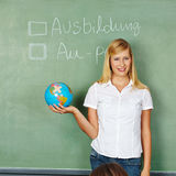 Apprenticeship or Au-Pair. Woman with globe in front of chalkboard with German words for Apprenticeship and Au-Pair written on it stock photography