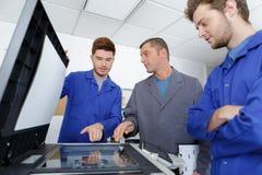 Apprentis apprenant à fixer le photocopieur photographie stock