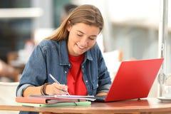 Apprentissage en ligne d'étudiant prenant des notes dans une barre Photos libres de droits