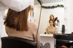 Apprettatrice dei capelli che fa stile per un cliente femminile fotografie stock