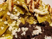 Approach to plate of chilaquiles in green sauce with strips of roasted chicken and refried beans, traditional mexican food. Approach plate chilaquiles green stock photography
