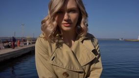 Approach to Attractive Young Blonde Woman in Trench with Vintage Suitcase is Sitting on the Jacht Pier. Approach to Attractive Young Blonde Woman in Tranch and stock video footage