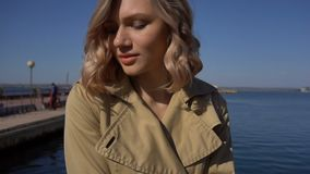 Approach to Attractive Young Blonde Woman in Trench with Vintage Suitcase is Sitting on the Jacht Pier. Approach to Attractive Young Blonde Woman in Tranch and stock footage