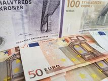 Approach to danish banknotes and euro bills. Europe, european, dkk, denmark, kroner, crowns, commerce, exchange, travel, trade, trading, value, buy, sell stock photo