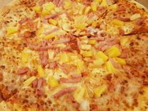 approach to a hawaiian pizza, with ham, cheese and pineapple chunks stock photos